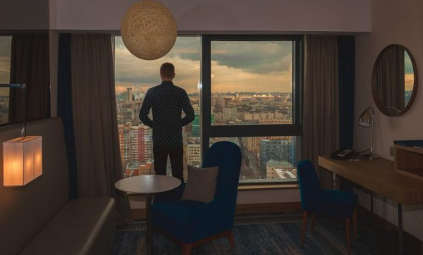 Young business man on the background of the panoramic windows with the view on the city from the hotel room at sunset time
